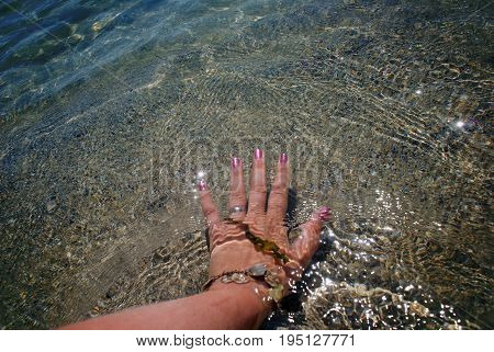Female Left Hand With Pink Manicure Touches The Water In The Clear Sea