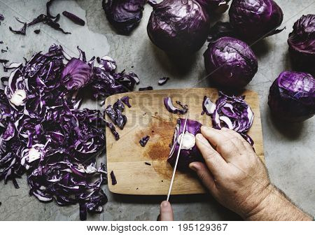 Hands using a knife chopping red cabbage