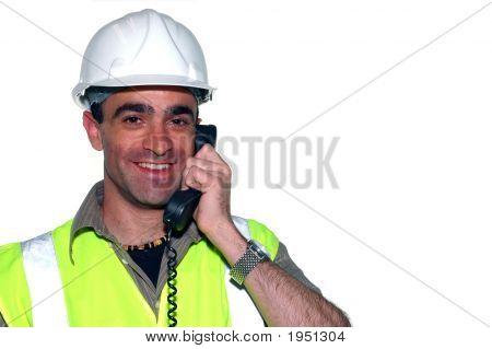 Lachende bouwvakker met een telefoon