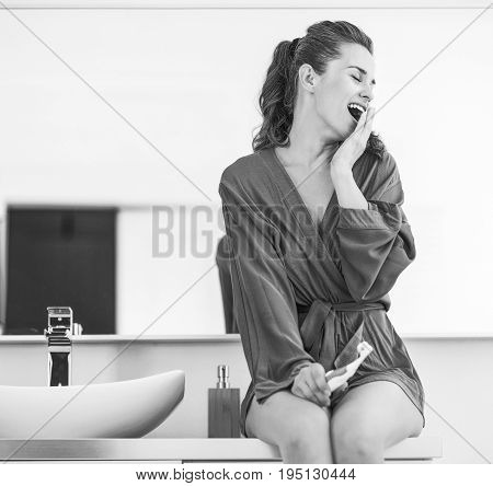 Young modern woman with toothbrush in bathroom yawning
