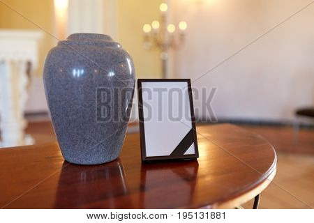 funeral and mourning concept - photo frame with black ribbon and cremation urn on table in church