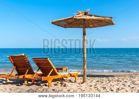 Two sunbeds and straw umbrella on the sand beach at the sea summer sea rest concept.
