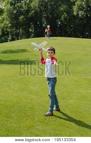 Cute Little Boy Playing With Toy Plane On Green Meadow In Park