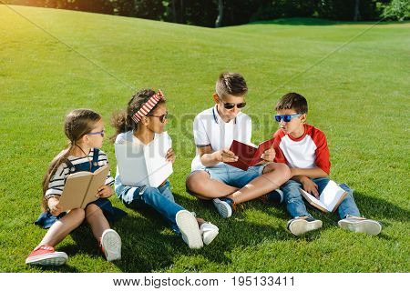 Adorable Multiethnic Kids In Sunglasses Reading Books On Green Meadow In Park