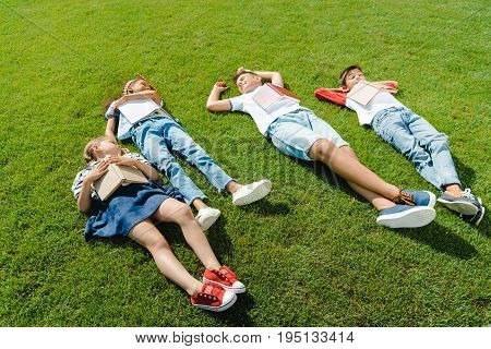 High Angle View Of Cute Multiethnic Kids Lying On Green Meadow With Books