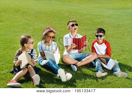Cheerful Multiethnic Kids In Sunglasses Reading Books While Sitting On Green Grass