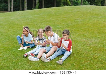 Cute Multiethnic Children Playing With Soap Bubbles While Sitting Together On Grass