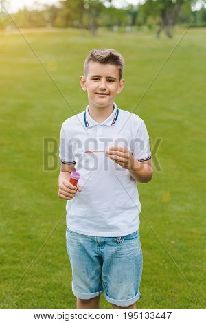 Cute Boy Playing With Soap Bubbles And Smiling At Camera In Park