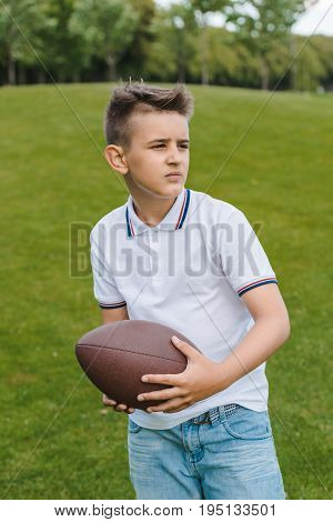 Cute boy in polo shirt holding rugby ball and looking away in park