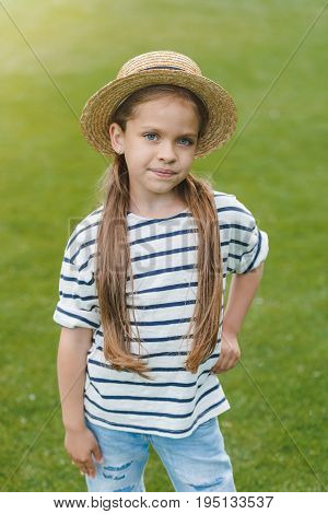 Adorable Little Girl In Straw Hat Standing With Hand On Waist And Looking At Camera In Park