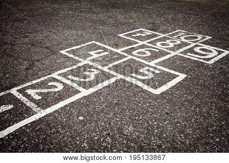 Hopscotch court with numbers from 1 to 10 drawn with white paint on the asphalt
