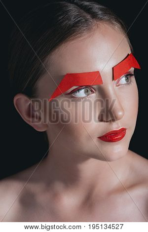 Portrait Of Stylish Woman With Red Lips And Paper Brows Posing For Fashion Shoot Isolated On Black