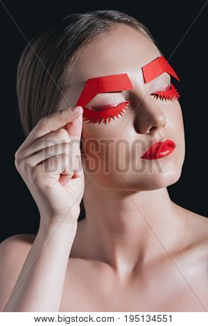 Woman Holding Red Paper Brows Near Face Posing For Fashion Shoot Isolated On Black