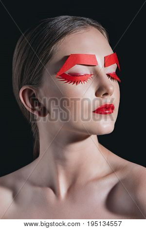 Portrait Of Woman With Red Paper Eyelashes And Brows Posing For Fashion Shoot Isolated On Black
