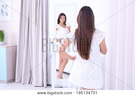 Pregnant woman standing near mirror and taking selfie