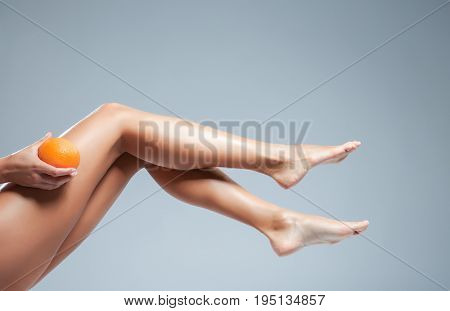 Female legs and orange on grey background. Cellulite problem concept