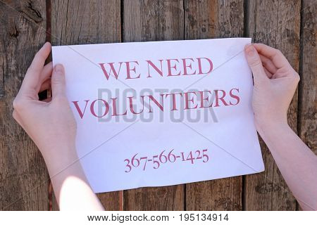 Woman sticking paper with text WE NEED VOLUNTEERS on wooden fence