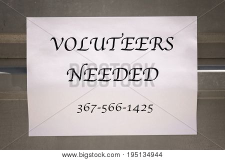 Announcement with text VOLUNTEERS NEEDED on metal fence