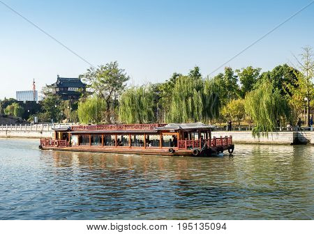 Suzhou, China - Nov 5, 2016: View of the tower building and Waicheng River as viewed from a nearby public park. A tourist sightseeing river boat approaching.