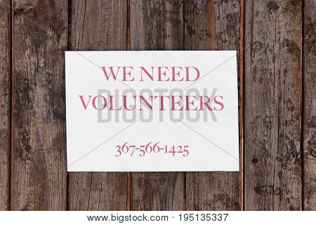 Announcement with text WE NEED VOLUNTEERS on wooden background