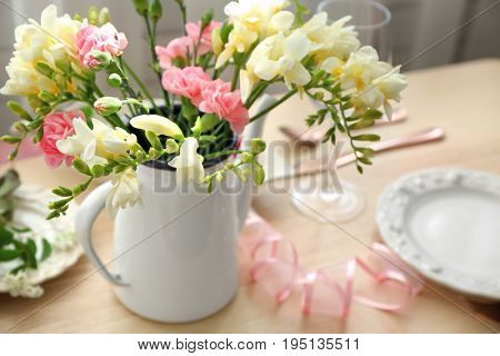 Beautiful composition with fresh freesia in vase on table