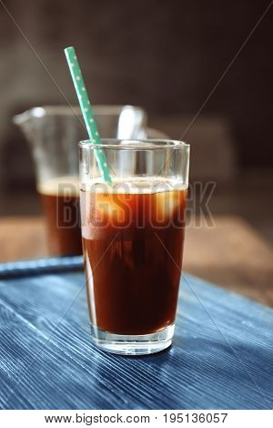 Glass with cold brew coffee and straw on table