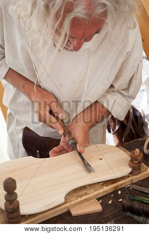 Luthier working on the creation of a stringed instrument. He uses a chisel to carve the top.