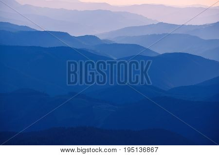 Carpathian mountains summer sunset landscape with abstract gradient of mountain peaks in blue colors, natural travel outdoor background