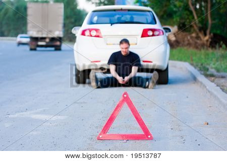 Young man sends an sms sitting by a white car. Focus is on the red triangle sign