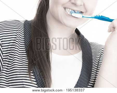 Woman brushing cleaning teeth close up. Funny girl with toothbrush. Oral hygiene. Toned image
