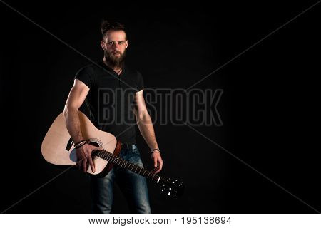 A Charismatic And Stylish Man With A Beard Stands With An Acoustic Guitar On A Black Isolated Backgr