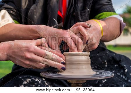 Pottery. Men's Hands Make A Clay Jug Or Pot On The Machine. He Is Helped By Women's Hands. A Man In