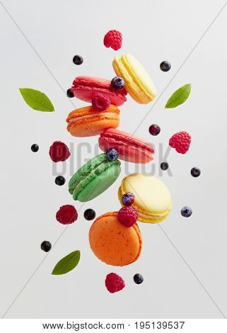 French macarons with fresh berries. Colorful macarons cakes with raspberries and blueberries.