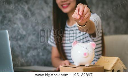 Happy woman saving money in a piggybank Saving money concept