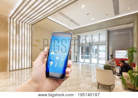 mobile phone with app on smart home in spacious hall of modern office building