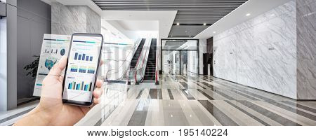 smart phone with mobile office in center of modern office building