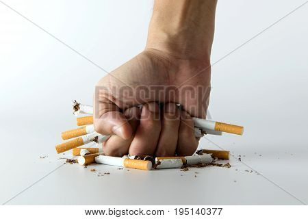 Fist crashing cigarettes for quit smoking concept