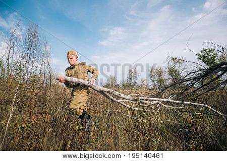 Dyatlovichi, Belarus - October 1, 2016: Man Reenactor Dressed As Russian Soviet Red Army Infantry Soldier Of World War II Equips Camp Prepares Wood For Fire At Historical Reenactment