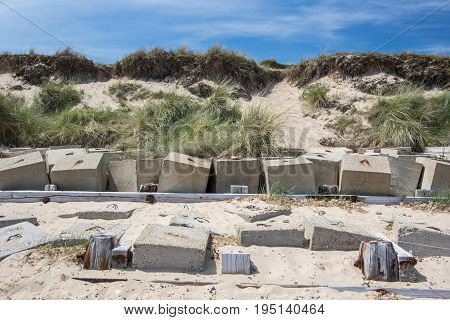 Coastal erosion management with concrete blocks. Sea defences in front of vulnerable beach cliff face.