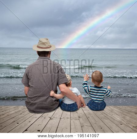Father and his 2 sons sitting on a pier by the sea and watching the rainbow