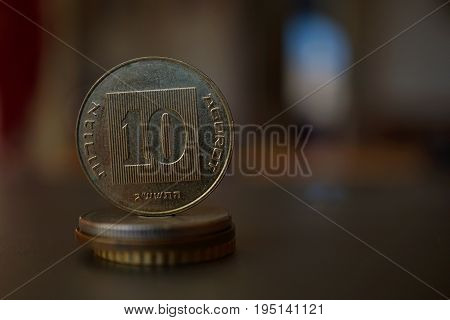 Macro detail of a metal Israeli coin (10 Shekels, ten ILS) on the top of column created of coins with a positive colorful warm background