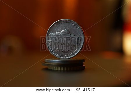 Macro detail of an American coin (five cents of American dollar, USD) on the top of column created of coins with a positive colorful warm background