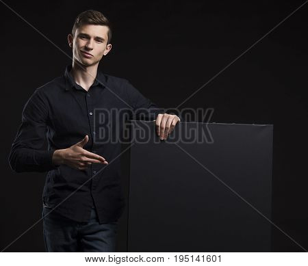 Young sexy man portrait of a confident businessman showing presentation, pointing placard black background. Ideal for banners, registration forms, presentation, landings, presenting concept.