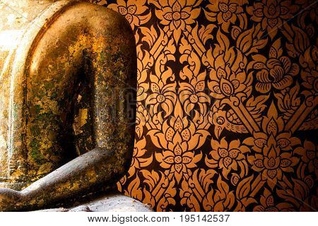 BANGKOK, THAILAND - JULY 9, 2017: Native Thai Buddha statue and Thai painted style of textured wall in ancient Buddhist temple. Thai general line art pattern  in Wat Intharam temple Thonburi in Bangkok, Thailand.