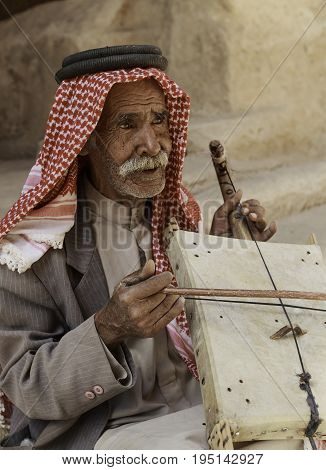 Little Petra Jordan - June 20 2017: Old Bedouin man or Arab man in traditional outfit playing his musical instrument at the doorway of Little Petra.