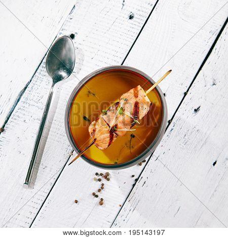 Restaurant Soup Food - Cream of Pumpkin Soup with Grilled Fish. Gourmet Restaurant Soup Menu. Bowl of Pumpkin Soup on White Wooden Backgound