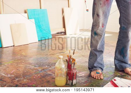 Low section of a male artist standing by paint brushes and paint thinner in studio