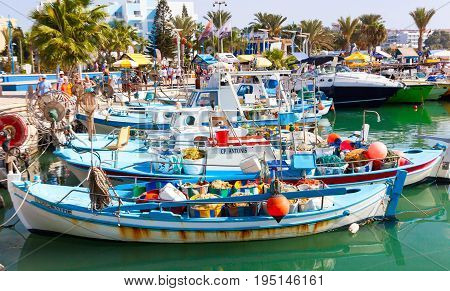 CYPRUS AYIA NAPA - SEPTEMBER 20 2016: Harbor near Ayia Napa. Fishing boats palms and tourists.