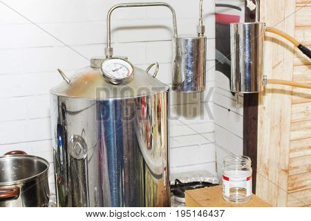 moonshine still in action at home. alcohol mashine