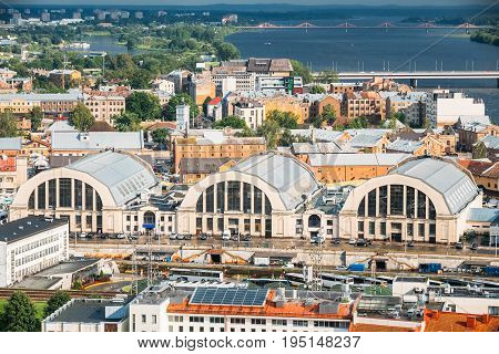 Riga, Latvia. Aerial Cityscape In Sunny Summer Evening. Top View Of Landmarks - Bus Station Riga International Coach Terminal And Riga Central Market
